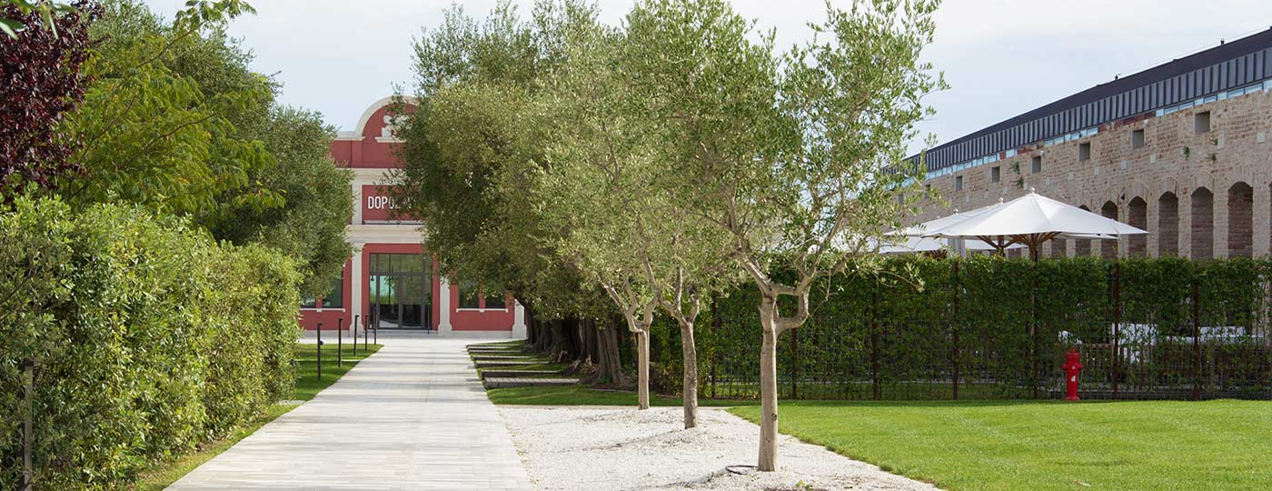 Natural stone paved driveway made by Stone Concept surrounded by trees and plants and leading to a red building